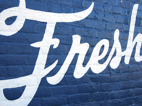 "Image of the word ""Fresh"" painted on a brick wall."