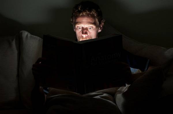 Image of a man reading a book, which is emitting light