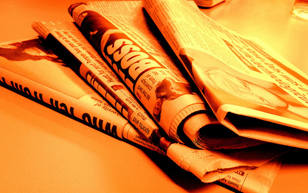 An image of newspapers with an orange tint