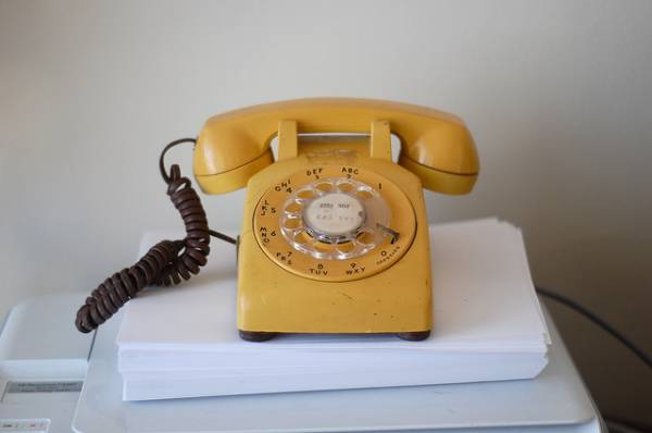 An image of a yellow rotary telephone