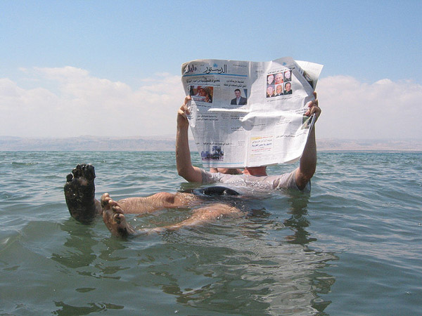 Photo of a guy reading a newspaper in the water.