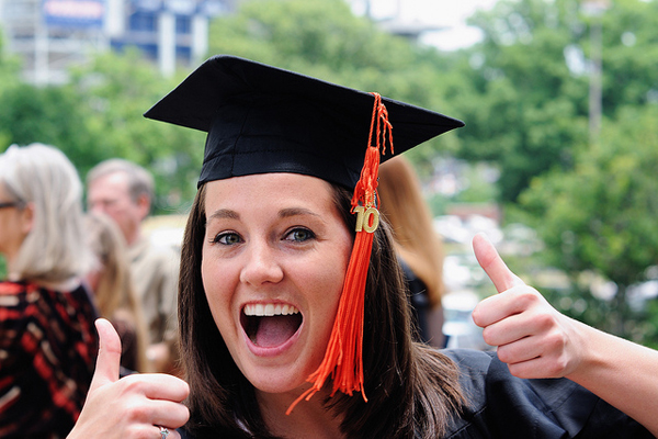 Photo of a girl giving the thumbs-up after graduating