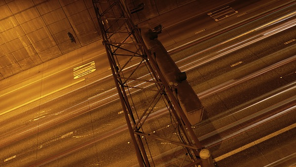 Image of a highway at night, with light entrails from cars.